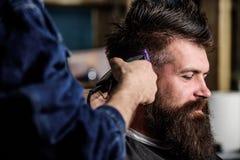 Zakładu fryzjerskiego pojęcie Ręki fryzjer męski z włosianym cążki, zamykają up Modnisia brodaty klient dostaje fryzurę Fryzjer m Zdjęcia Stock