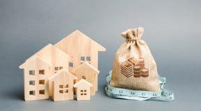 Zak met geld en meetlint met blokhuizen Het concept een beperkte onroerende goederenbegroting Lage subsidies Gebrek van royalty-vrije stock afbeelding