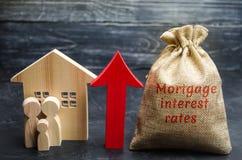 Zak met het geld en de rentevoeten van de woordhypotheek en op pijl met familie en huis Het opheffen van hypotheektarieven en bel royalty-vrije stock foto