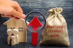 Zak met het geld en de rentevoeten van de woordhypotheek en op pijl met familie en huis Het opheffen van hypotheektarieven en bel royalty-vrije stock afbeelding