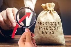 Zak met het geld en de rentevoeten van de woordhypotheek en op pijl in mannelijke handen Het opheffen van hypotheektarieven en be royalty-vrije stock foto's