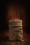 Zak met koffiebonen wordt gevuld in schijnwerper die Royalty-vrije Stock Fotografie
