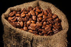 Zak met koffiebonen wordt gevuld in schijnwerper die Royalty-vrije Stock Foto's