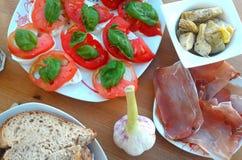 Zakąska na stole, serze, pomidorze, karczochu i czosnku, Fotografia Stock