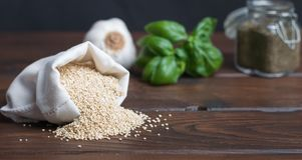 Zak van quinoa met knoflook, tomaten en kruiden Stock Foto