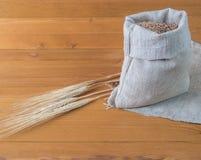 Zak van tarwe en oren op een houten achtergrond Royalty-vrije Stock Afbeelding