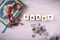 Zakat concept: Quran and tasbih with jar full of coins