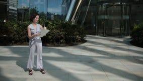 Zakelijk, jonge vrouw, brunette, een smartphone aan het praten, een positieve houding stock video