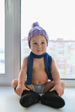 Zakelijk weared weinig comfortabele zitting van de babyjongen dichtbij het venster in de winterkleren stock afbeelding