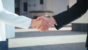 Zakelijke mensen die handen schudden Handshake tussen zakenman en zakenvrouw in de openlucht door kantoorgebouwen stock videobeelden