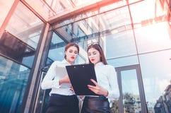 Zaken Dame #37 Bureaupersoneel Twee jonge meisjes met elektronisch lusje Stock Afbeeldingen