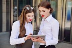 Zaken Dame #37 Bureaupersoneel Twee jonge meisjes met elektronisch lusje Stock Foto's