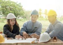 Zaken, de bouw, groepswerk en mensenconcept - de groep bespreekt de projectbouwtekening met zijn bedrijfscliënt stock foto's