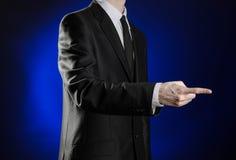 Zaken en de presentatie van het thema: mens in een zwart kostuum die handgebaren op een donkerblauwe geïsoleerde achtergrond in s Royalty-vrije Stock Foto