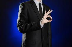 Zaken en de presentatie van het thema: mens in een zwart kostuum die handgebaren op een donkerblauwe geïsoleerde achtergrond in s Stock Foto