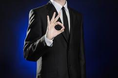 Zaken en de presentatie van het thema: mens in een zwart kostuum die handgebaren op een donkerblauwe geïsoleerde achtergrond in s Royalty-vrije Stock Afbeeldingen