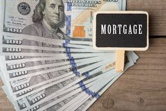 Zaken en financieel concept - honderd dollarsrekeningen en weinig bord met woordhypotheek stock afbeeldingen