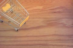 Zaken en Financieel Concept: Hoogste mening die van geel miniboodschappenwagentje of supermarktkarretje op houten vloer plaatsen Stock Foto