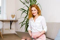 Zaken en opleiding de mooie jonge rode haired lange haar Kaukasische vrouw gebruikt laptop terwijl het zitten op bank in ruimte Z royalty-vrije stock foto's