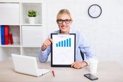 Zaken en statistiekenconcept - vrolijke bedrijfsvrouwensittin stock foto