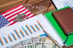 Zaken en winstenconcept met grafiek, dollar, muntstukken en notitieboekje Stock Foto's