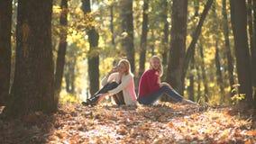 Zaken openlucht Het werken in aard De herfstportret van mooie studenten in het park Het gebladerte van de daling Twee Zusters stock videobeelden