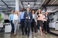 Zaken Team Walking Office Full Length, Zakenluigroep met Leider In Foreground Moving vooruit door Modern stock foto