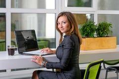 Zaken, technologie en groen bureauconcept - jonge succesvolle onderneemster met laptop computer op kantoor Vrouw die tablet gebru Stock Afbeelding