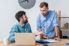 Zakenlieden die bespreking hebben op het werk terwijl het werken met laptop in bureau Stock Fotografie