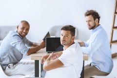 Zakenlieden die bij werkplaats met laptop in bureau zitten Royalty-vrije Stock Fotografie