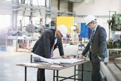 Zakenlieden die blauwdruk onderzoeken bij werkbank in de metaalindustrie stock foto's