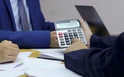 Zakenlieden die calculators drukken en met vrienden communiceren om baaninformatie te analyseren royalty-vrije stock afbeelding