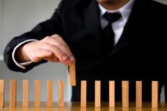 Zakenlieden die domino's plukken om de ontbrekende domino's te vullen Groeiend bedrijfsconcept royalty-vrije stock afbeeldingen