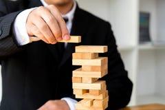 Zakenlieden die dominoe blokken plukken om de ontbrekende domino's te vullen stock fotografie