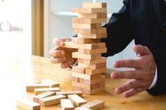 Zakenlieden die dominoe blokken plukken om de ontbrekende domino's a te vullen stock afbeelding
