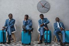 Zakenlieden die in een wachtkamer met koffers zitten, zelfde mens stock foto's
