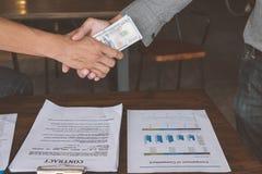Zakenlieden die handdruk met geld in handen maken, Corruptie en royalty-vrije stock foto's