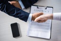Zakenlieden die handen met contract op lijst schudden royalty-vrije stock afbeelding