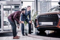 Zakenlieden die hun knieën buigen terwijl het bekijken de bodem van auto royalty-vrije stock foto