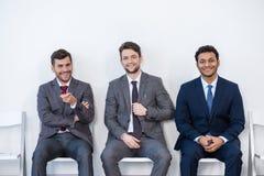 Zakenlieden die in kostuums op stoelen bij witte wachtkamer zitten royalty-vrije stock fotografie