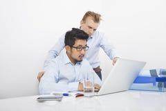 Zakenlieden die laptop met behulp van samen bij bureau in bureau Royalty-vrije Stock Foto's