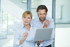 Zakenlieden die met laptop op kantoor werken, die copyspace, succesvolle zaken bespreken Stock Afbeeldingen