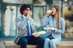 Zakenlieden die met sandwiches voor het bureaugebouw zitten - middagpauze, selectieve nadruk royalty-vrije stock foto's