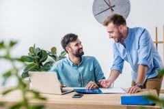Zakenlieden die nieuw project bespreken op het werk met laptop Stock Afbeelding