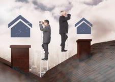 Zakenlieden die op bezitsladder huispictogrammen bekijken over dak Stock Fotografie