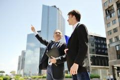Zakenlieden die over het werkproject spreken op achtergrond moderne bureau collectieve gebouwen Stock Foto