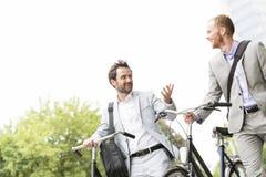 Zakenlieden die terwijl in openlucht het lopen met fietsen spreken stock foto