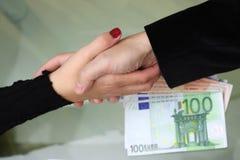 Zakenlieden en onderneemsterhanddruk met geld op bureau stock foto