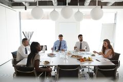 Zakenlieden en Onderneemsters die in Moderne Bestuurskamer bij Werkende Lunch samenkomen stock afbeelding