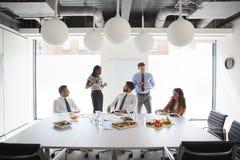 Zakenlieden en Onderneemsters die in Moderne Bestuurskamer bij Werkende Lunch samenkomen royalty-vrije stock afbeeldingen